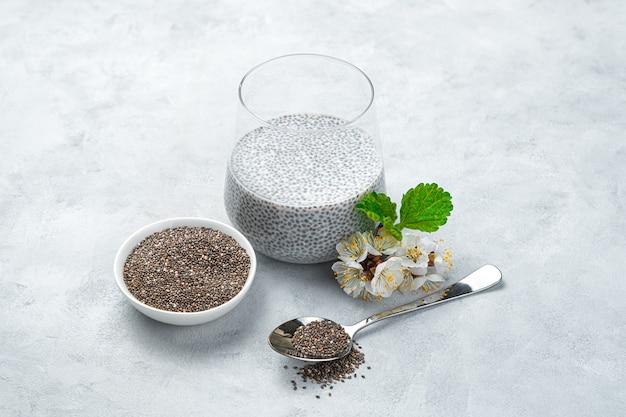 Budino con latte di cocco e semi di chia in un bicchiere, semi con una tazza e un cucchiaio su una parete grigia. vista laterale, orizzontale. dolci sani.