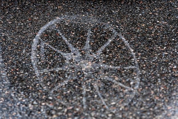 Pozzanghera sul marciapiede con un riflesso della ruota dell'auto, primo piano