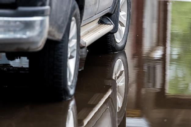 Pozzanghera sul marciapiede con il riflesso di un'auto parcheggiata, primo piano, strada dopo la pioggia