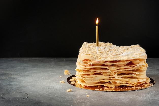 Torta di pasta sfoglia napoleone con una candela accesa dorata