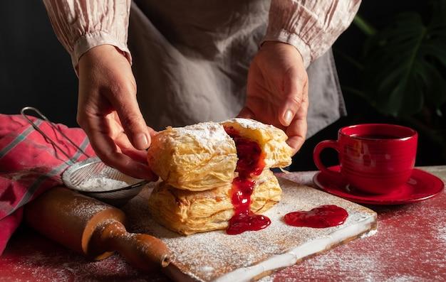 Pasta sfoglia dessert marmellata rossa mano viburno ciliegia tazza caffè sfondo nero