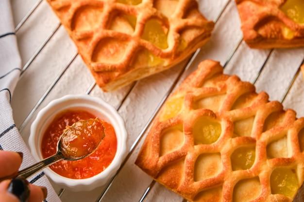 Mini torte di pasta sfoglia con ripieno di marmellata di pere e lime su un piatto bianco su una griglia per arrosti con fresco con fette di pera e lime, mano femminile con un cucchiaio