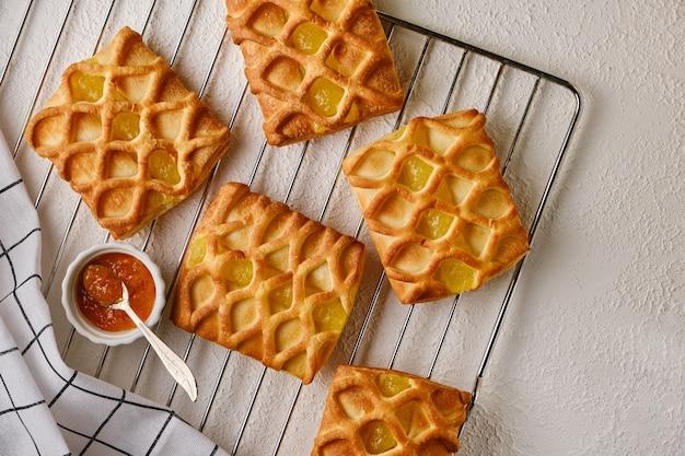 Mini torte di pasta sfoglia con ripieno di marmellata di pere e lime su griglia per arrosti con fresco con fette di pera e lime, vista orizzontale dall'alto, flatlay