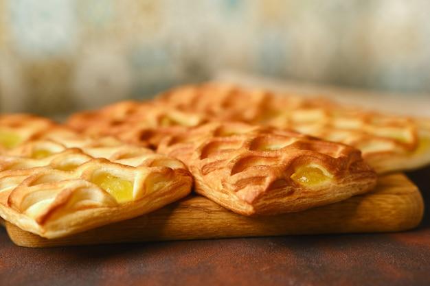 Mini torte di pasta sfoglia con ripieno di marmellata di pere e lime su un piatto bianco su un tavolo di cemento con fresco con fette di pera e lime, vista orizzontale dall'alto, flatlay