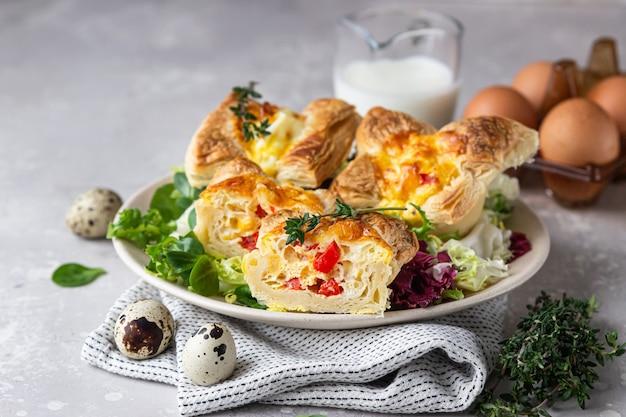 Mini quiche di pasta sfoglia, torta o crostata con verdure servite su un piatto con insalata mista.