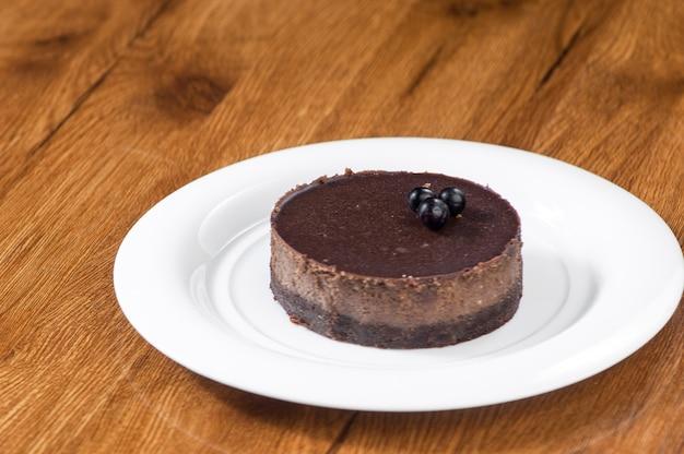 Pasta sfoglia in un piatto bianco rotondo su una superficie di legno con riflessione