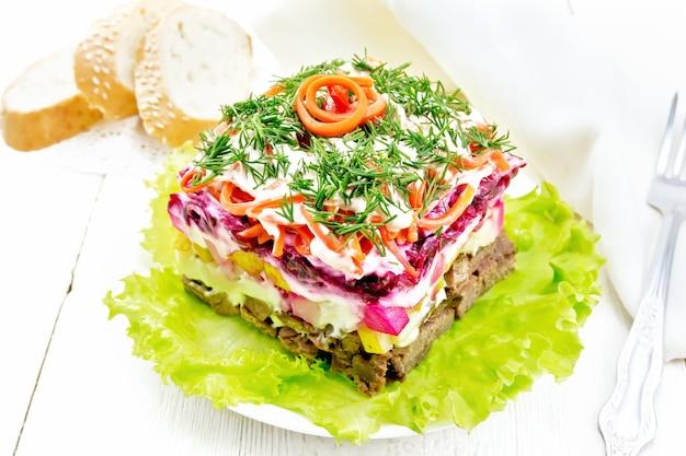 Insalata di pasta sfoglia con carne di manzo, patate lesse, pere, carote coreane piccanti, condita con maionese e guarnita con aneto su lattuga verde nel piatto