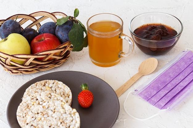 Torte di riso soffiato, una fragola sul piatto, una tazza di tè, una ciotola di vetro con marmellata, un cesto di vimini con frutta e una maschera protettiva medica sullo sfondo bianco strutturato.