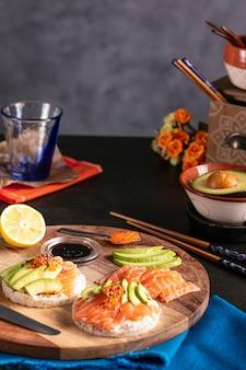 Riso soffiato spalmato con salmone crudo e avocado su un tavolo scuro