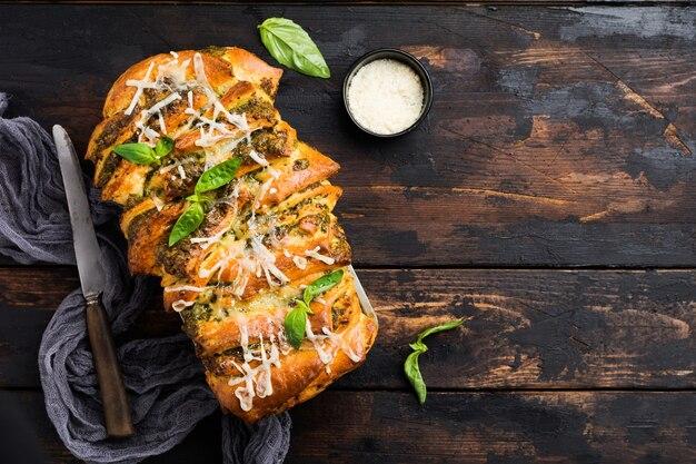 Pane a scomparsa con pesto di pasta italiana, basilico e parmigiano in forma di cottura su vecchio fondo di cemento scuro