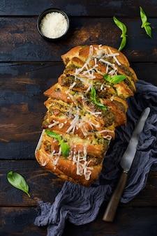 Pane pullapart con pesto di pasta italiana, basilico e parmigiano in forma di cottura su un vecchio fondo di cemento scuro