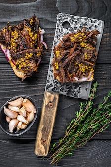 Panino tirato di maiale con carne di maiale affumicata su una mannaia di carne