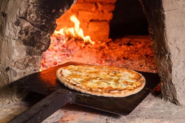 Tirare fuori una pizza ai quattro formaggi in un forno artigianale paraguaiano (tatakua).