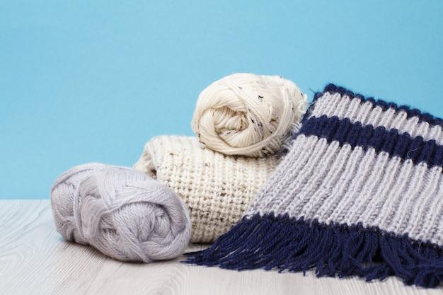 Pullover, sciarpa e matasse di filo con ferri da maglia in metallo su tavole grigie e sfondo blu. concetto di maglieria.