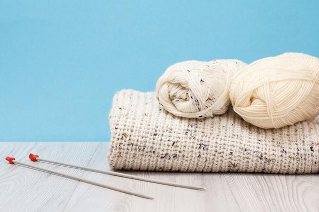 Pullover e matasse di filo con ferri da maglia in metallo su tavole grigie e sfondo blu. concetto di maglieria.