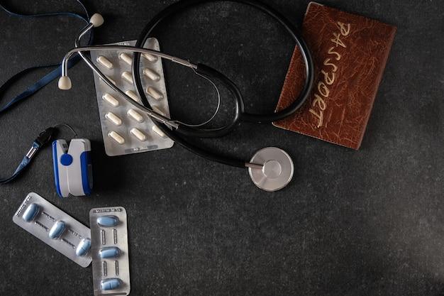 Saturimetro, misuratore di ossigeno nel sangue, termometro elettronico, passaporto, tonometro, pillole su una superficie grigia