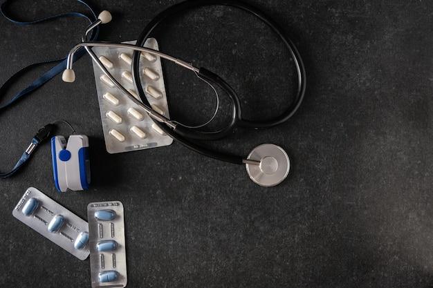 Saturimetro, misuratore di ossigeno nel sangue, termometro elettronico, tonometro, pillole su una superficie grigia