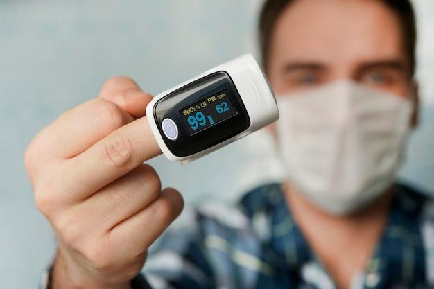 Pulsossimetro, dispositivo digitale da dito per misurare la saturazione di ossigeno nel sangue. la ridotta ossigenazione è un segnale di emergenza di polmonite, ad esempio causata dal coronavirus.