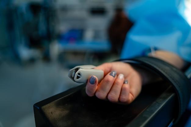 Saturimetro sul dito del paziente durante l'operazione chirurgica. paziente sdraiato sul letto d'ospedale. medicina, chirurgia, rianimazione, concetto di emergenza, clinica moderna. avvicinamento.