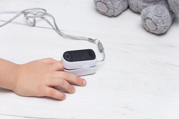 Pulsossimetro sul dito dei bambini per misurare la frequenza cardiaca e il livello di ossigeno su un tavolo di legno bianco. concetto sano.