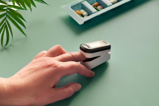 Dispositivo digitale portatile pulsossimetro per misurare la saturazione di ossigeno della persona. l'ossigenazione ridotta è un segnale di emergenza di polmonite che richiede assistenza medica immediata.