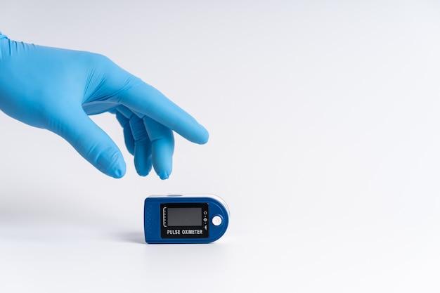 Ossimetro da polso su sfondo bianco. una mano in un guanto medico tiene un dispositivo per la diagnostica sanitaria.