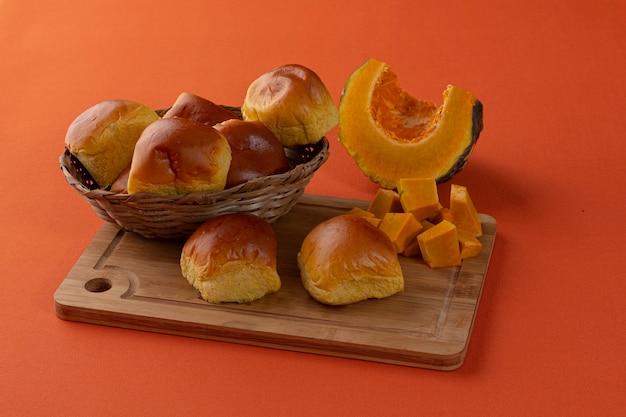 Pane di zucca sopra una tavola di legno e una zucca sullo sfondo su uno sfondo arancione