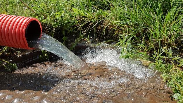 Pompaggio di acqua dalla zona alluvionale. sistema fognario. acque reflue industriali. scarichi fognari da un tubo di fognatura rosso ondulato in plastica in un tombino fognario in città.