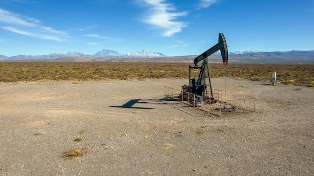 Pumpjack che estrae olio con sfondo montuoso