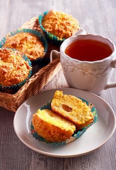 Muffin della mela e della zucca e tazza di tè sul tavolo