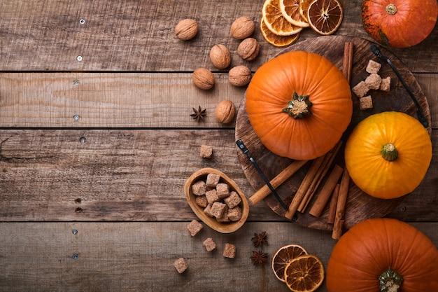 Zucca. sfondo di cibo autunnale con cannella, noci e spezie stagionali su fondo rustico. cucinare zucca o torta di mele e biscotti per il ringraziamento e le vacanze autunnali. vista dall'alto con copia spazio.