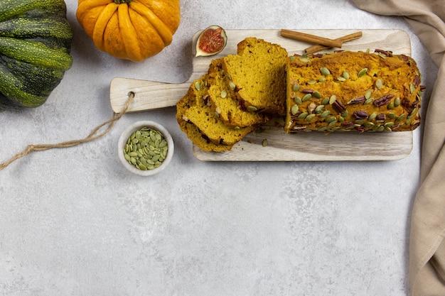 Pane alla zucca, torta su un tagliere di legno con noci pecan, semi di zucca e spezie alla cannella su una superficie grigio chiaro con zucche colorate e fichi