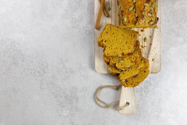 Torta di pane di zucca su un tagliere di legno con noci pecan e semi di zucca su uno sfondo chiaro