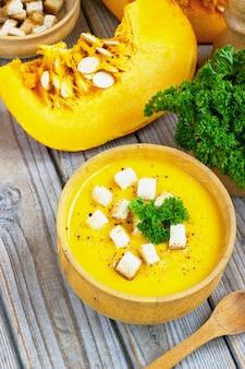 Zuppa di zucca e carote, tadka con panna e prezzemolo sul tavolo di legno scuro. vista dall'alto.