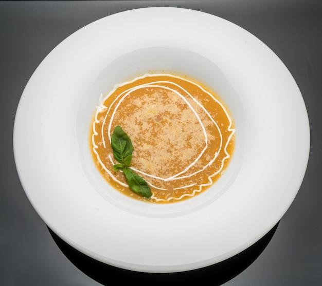 Zuppa di zucca e carota con panna e prezzemolo su fondo di legno scuro vista dall'alto