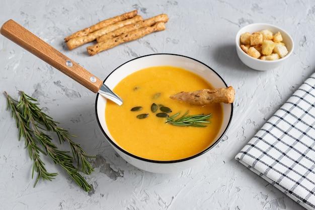 Zuppa di zucca e carote con panna, semi di zucca, crostini di pane e grissini grossini su fondo di legno dar k. stile rustico, messa a fuoco selettiva.