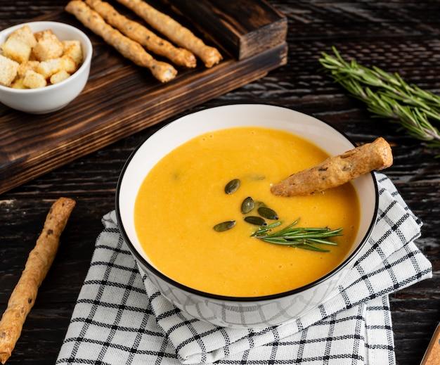 Zuppa di zucca e carote con panna, semi di zucca, crostini di pane e grissini grossini su fondo di legno scuro.