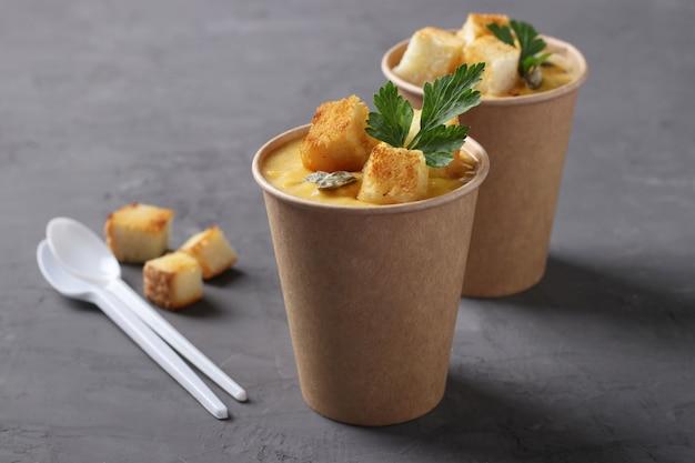 Zuppa di crema di zucca con crostini di pane e semi di zucca in tazze di carta artigianale su sfondo grigio.
