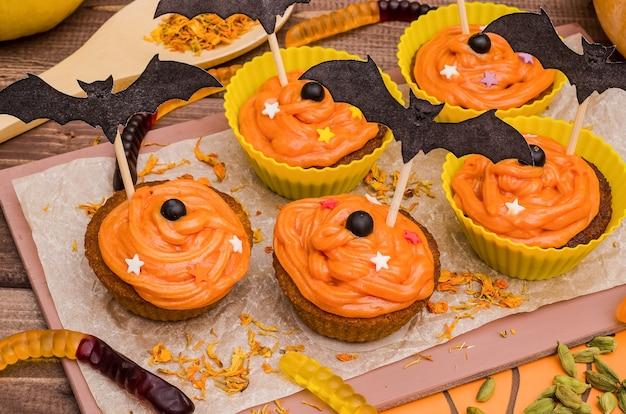 Cupcakes di zucca con crema all'arancia per halloween. idee per la cottura, dolci.