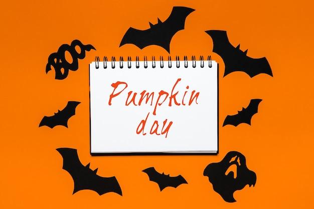 Giorno della zucca sulla superficie bianca e arancione con pipistrelli, zucche e fantasmi