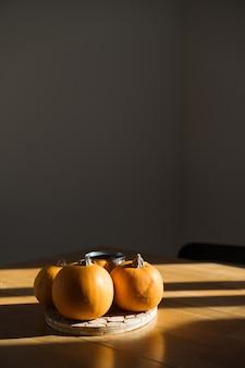 Decorazioni di zucca sulla tavola di legno a casa alla luce del sole. ombre del sole autunnale. halloween . foto di alta qualità