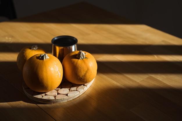 Decorazioni di zucca sulla tavola di legno a casa alla luce del sole.