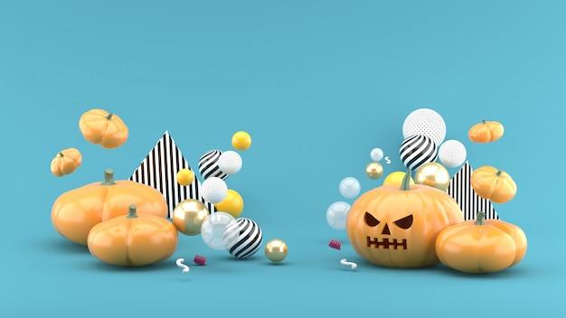 La zucca di halloween è tra le palline colorate nello spazio blu