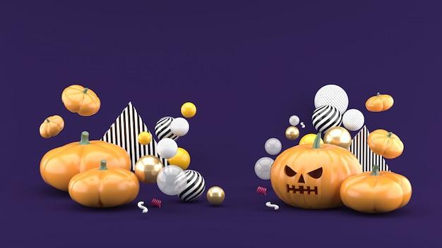La zucca di halloween è tra le palline colorate nello spazio viola