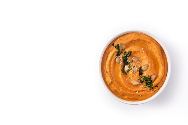 Hummus di zucca in una ciotola isolata su bianco