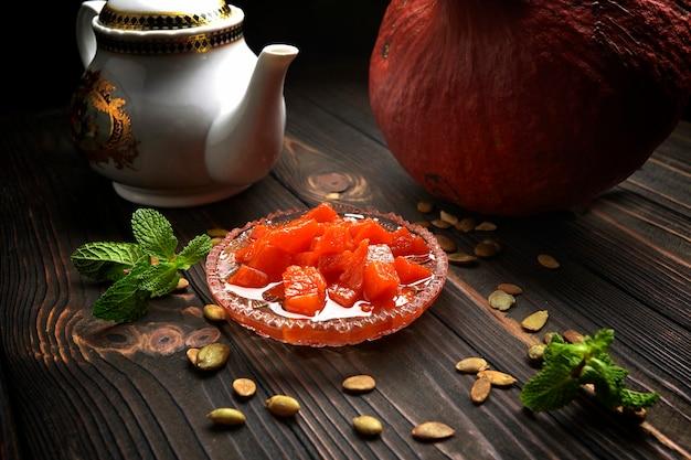 Marmellata di zucca, su un piano di legno scuro, con zucca, menta e semi di zucca