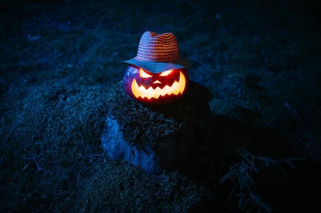 Lanterna di zucca con una terrificante faccia scolpita in un cappello su un concetto di moncone di muschio della vacanza di halloween