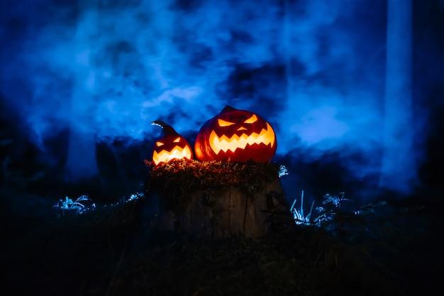 Lanterne di zucca con martinetti scolpiti volti sul tradizionale festival dell'orrore nella foresta con fumo