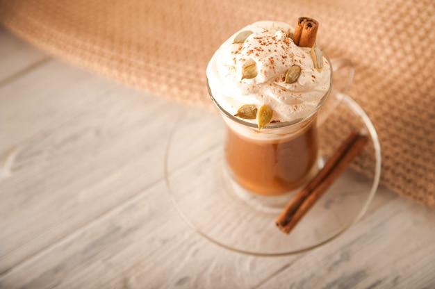 Latte di zucca in una tazza trasparente closeup e copia spazio latte con crema cannella zucche semi di zucca su un piatto bianco latte e maglione