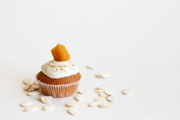 Muffin di zucca su uno sfondo bianco con semi di zucca. Foto Premium